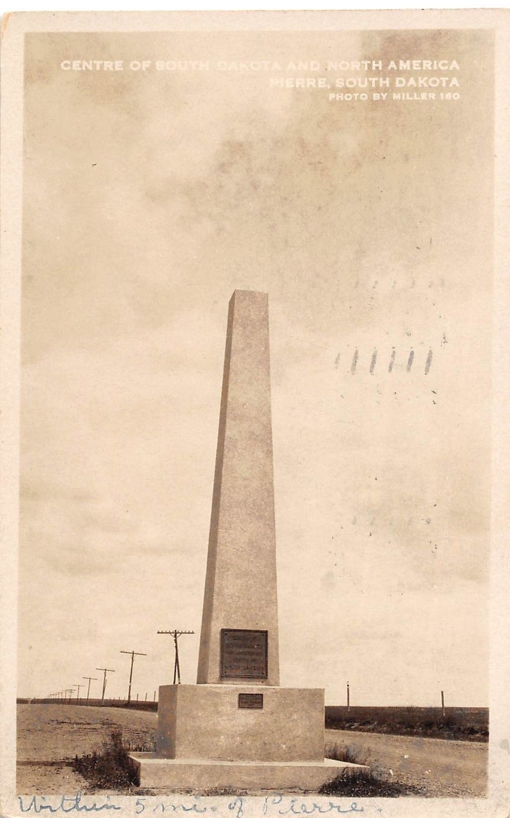A 1927 picture postcard shows the original monument in the center of the road.