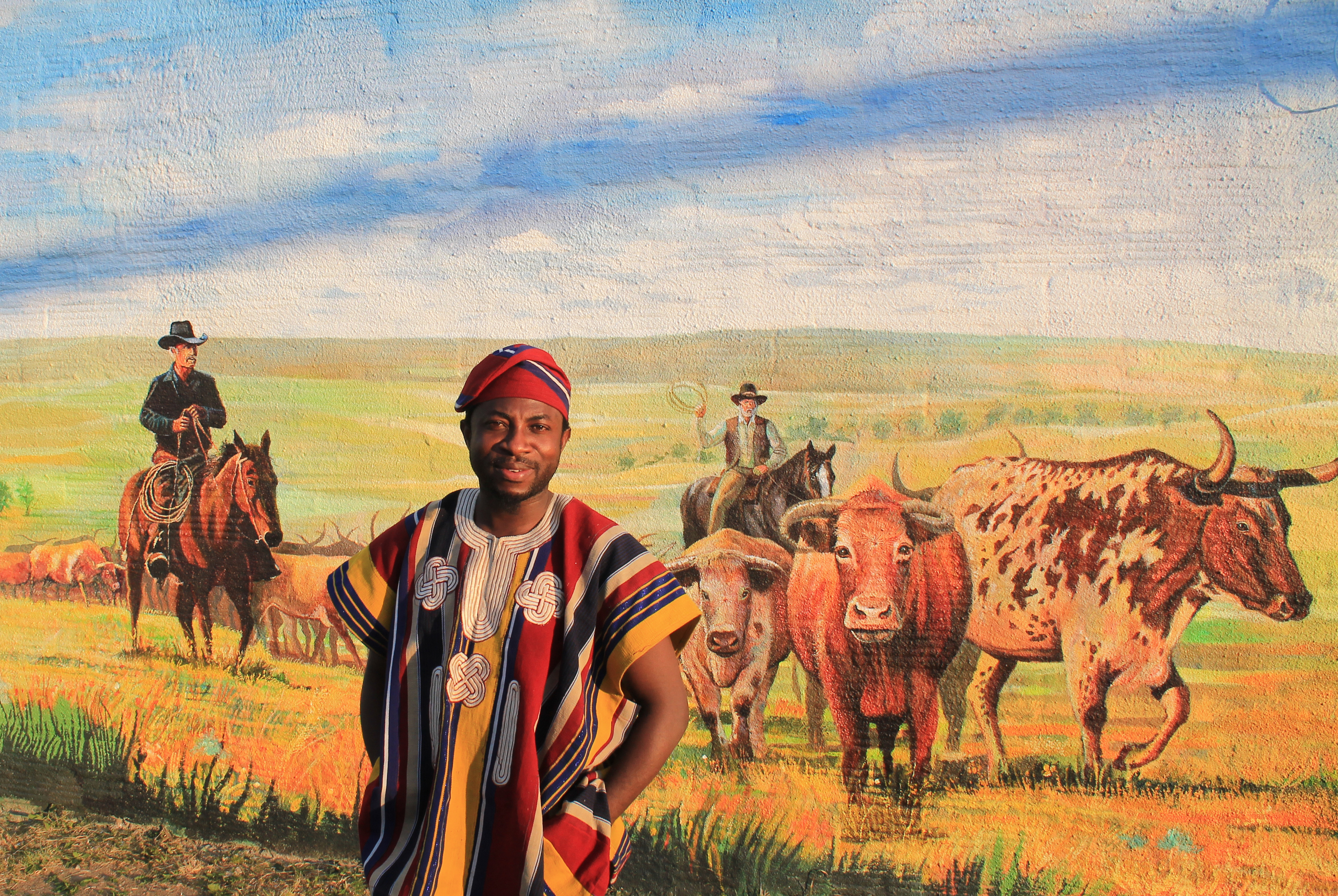 Dotun Popoola in front of the mural he painted with Jonathan Imafidor at Boss Cowman Square.