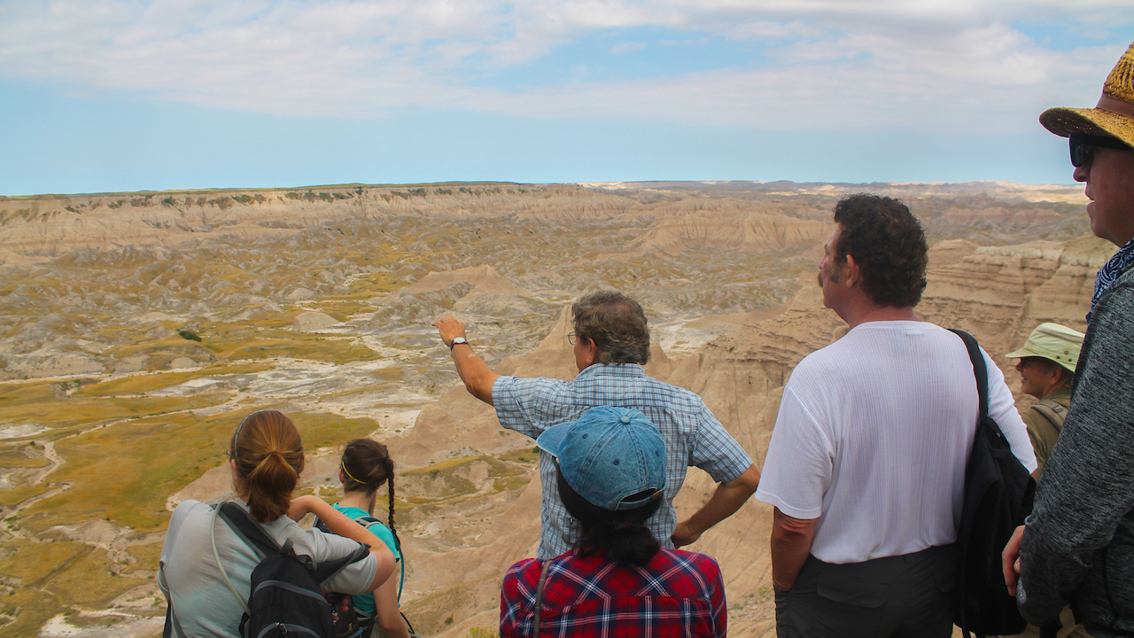 Badlands South Unit Ranger Richard Sherman points out table formations from atop Cedar Butte.