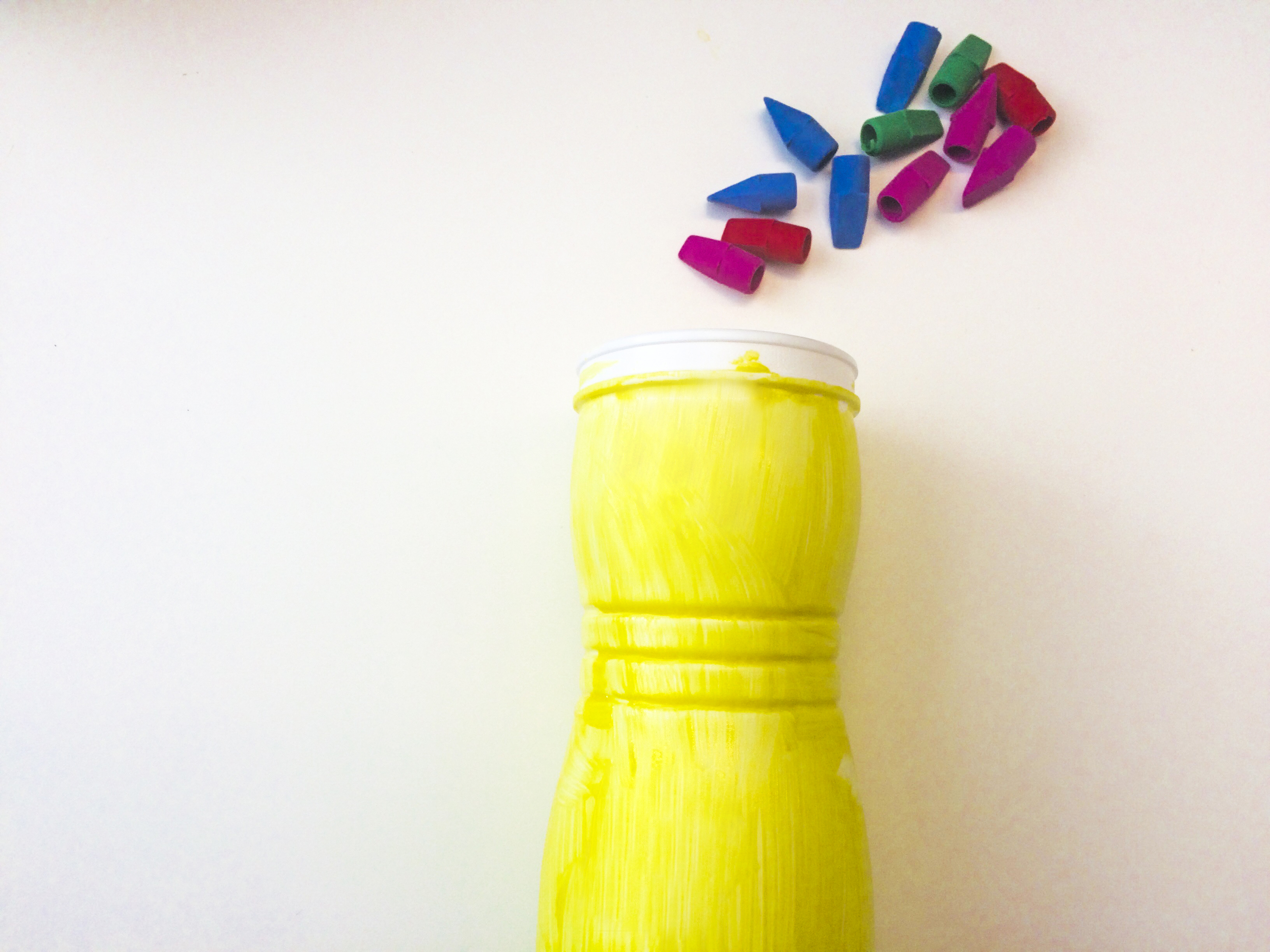 Yellow painted bottle with red, blue, and green erasers on top.