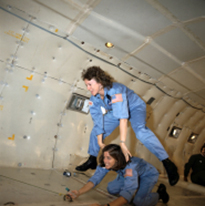 "Christa McAuliffe and Barbara Morgan preview microgravity during a special flight aboard NASA's KC-135 ""zero gravity"" aircraft."