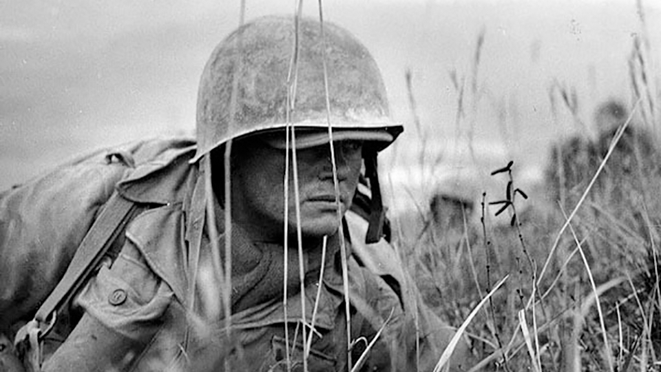An American soldier in the Korean War crawls through the grass and looks off into the distance.