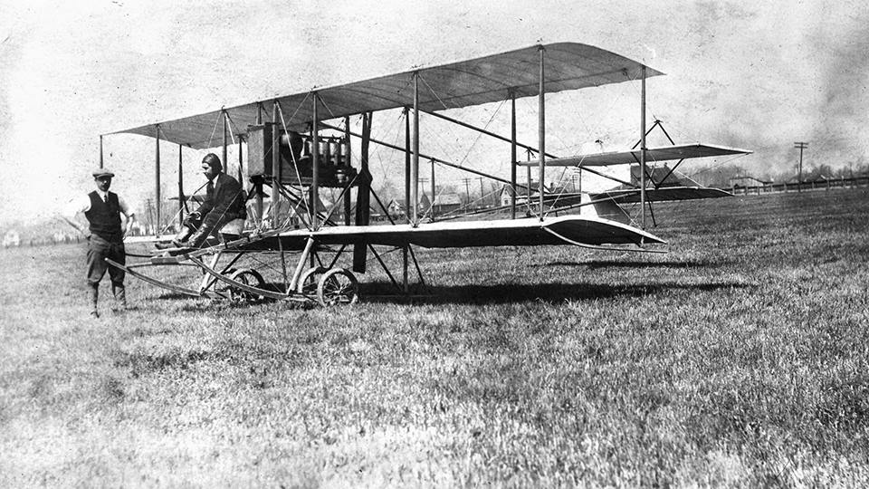 Lionel DeRemer sits at the controls of a biplane on the ground while another man stands nearby in a field.