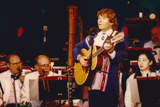John Denver performs with the National Symphony Orchestra, led by Maestro Erich Kunzel, on the 1995 National Memorial Day Concert.