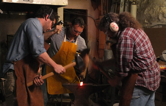 Veteran and artist Jeremiah Holland, metals instructor Davide Prete, and veteran and artist Tom Pullin forge at the anvil, Mark Markley photograph.