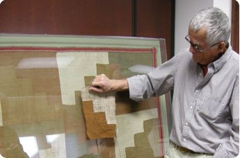 Weaver and professor Jim Bassler compares a piece of his own weaving to a textile made by the people of Nazca, Peru (200 BC-700AD)