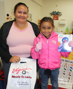 A mother and child receive an RFS dental health bag