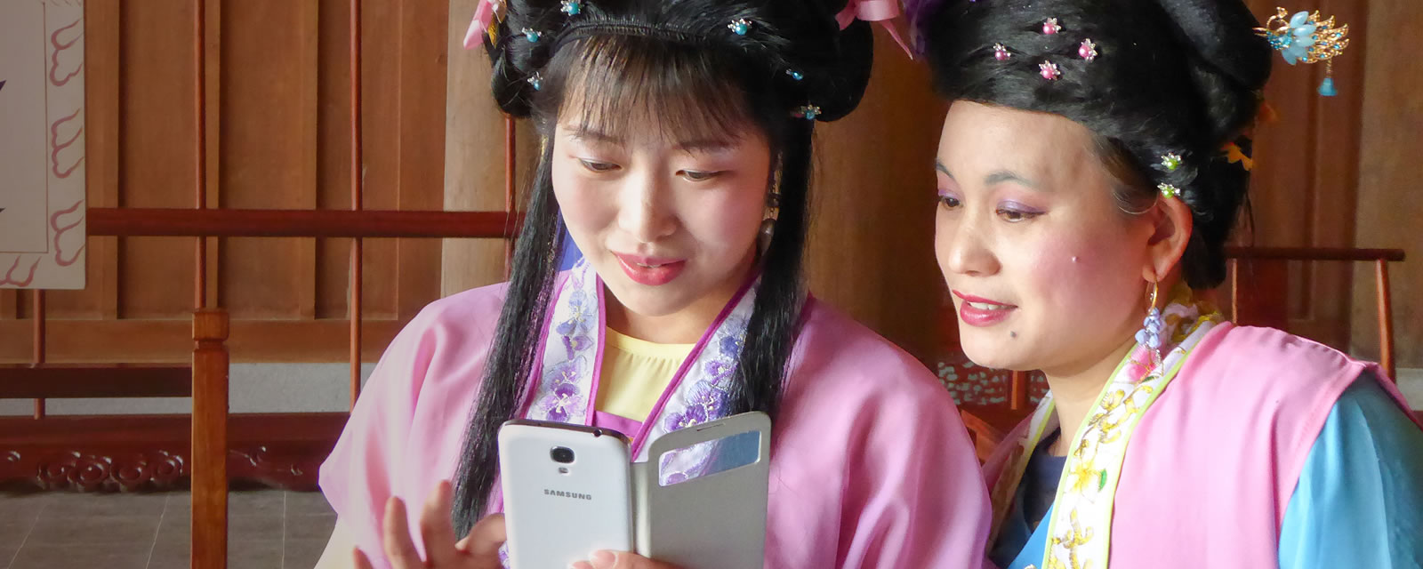 Two female actors in traditional Chinese wardrobe looking at a mobile phone at the Civic Hall in Huizhou