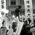 man with a bullhorn addressing a crowd of people