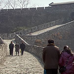people walking along a path on top of a wall