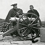 photo of Chinese men loading a canon