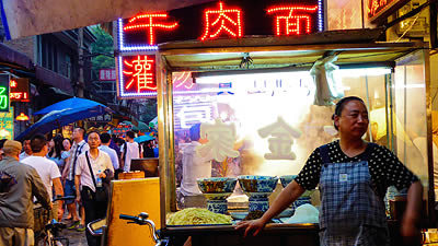 noodle vendor standing in front of cart of noodles and soup bowls