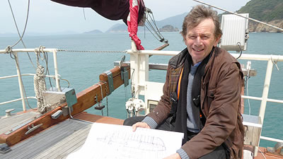 Michael Wood on a sail boat holding renderings of a Chinese boat