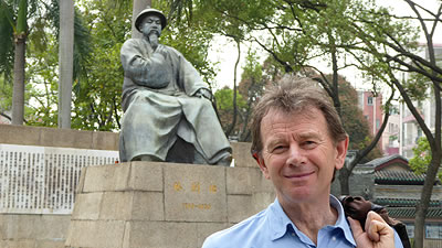 Michael Wood standing in front of a bronze statue