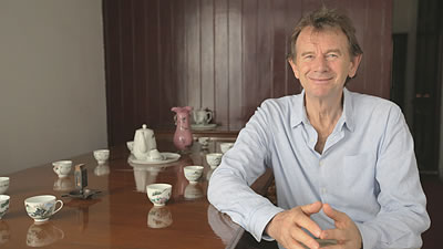 Michael Wood seated a table with tea cups and teapot