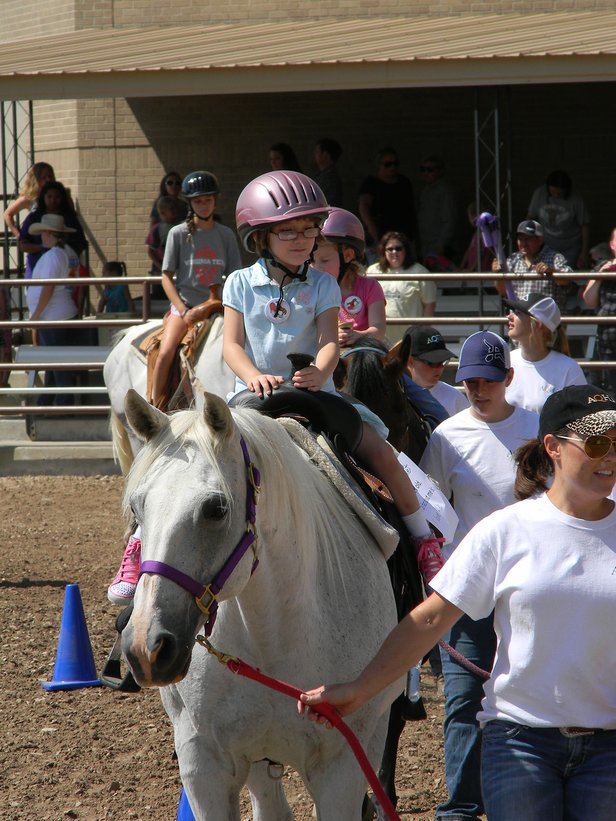 Volunteers lead children on a quarter horse ride at last year's National Day of the Cowboy celebrations.