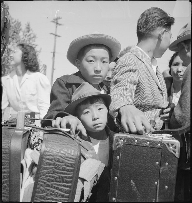 These young evacuees of Japanese ancestry are awaiting their turn for baggage inspection at this assembly center in Turlock, Calif., in this image taken by Dorothea Lange.