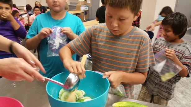 Students prepare zucchini muffins.
