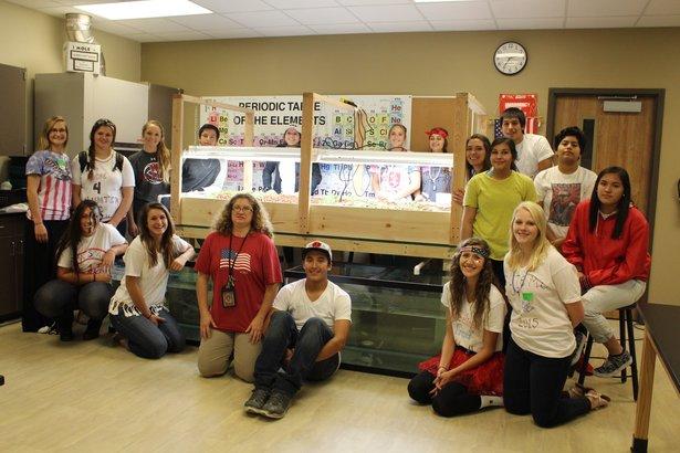 Students surround large classroom aquaponics system.