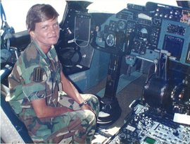 Linda Bray, the first woman to lead troops into battle, sits in a cockpit.
