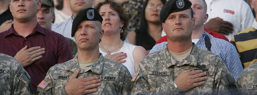 National guardsmen with hands on hearts during the national anthem