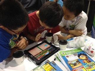Three boys playing PBS KIDS apps on an iPad