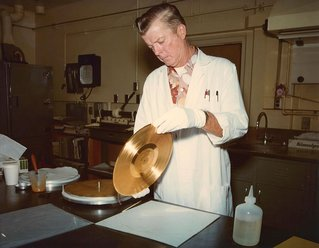 engineer holding Voyager's golden record