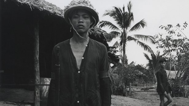 A black-and-white image of a Vietnamese man holding a gun, with a village in the background.