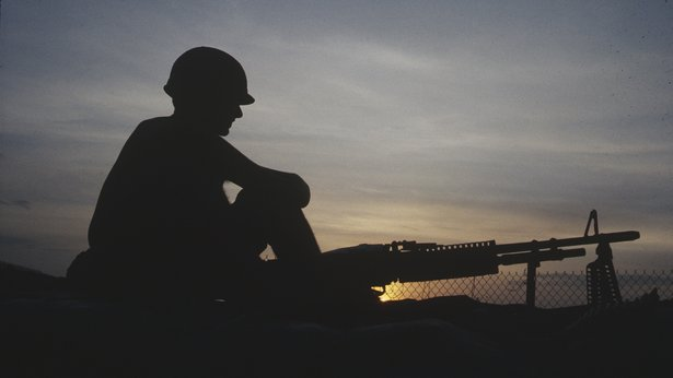 A color photo of a soldier, silhouetted in the foreground, while the sun sets in the background.
