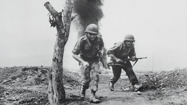 A black-and-white image showing two American servicemembers retreating from an explosion in the background.