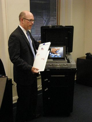 Casey gives a tutorial on the newer voting machines.