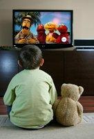 Child watching Sesame Street with stuffed bear