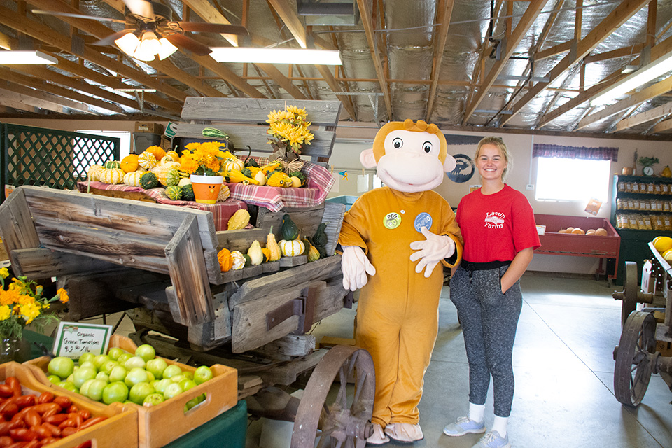 Image of Curious George at a farm stand with an employee