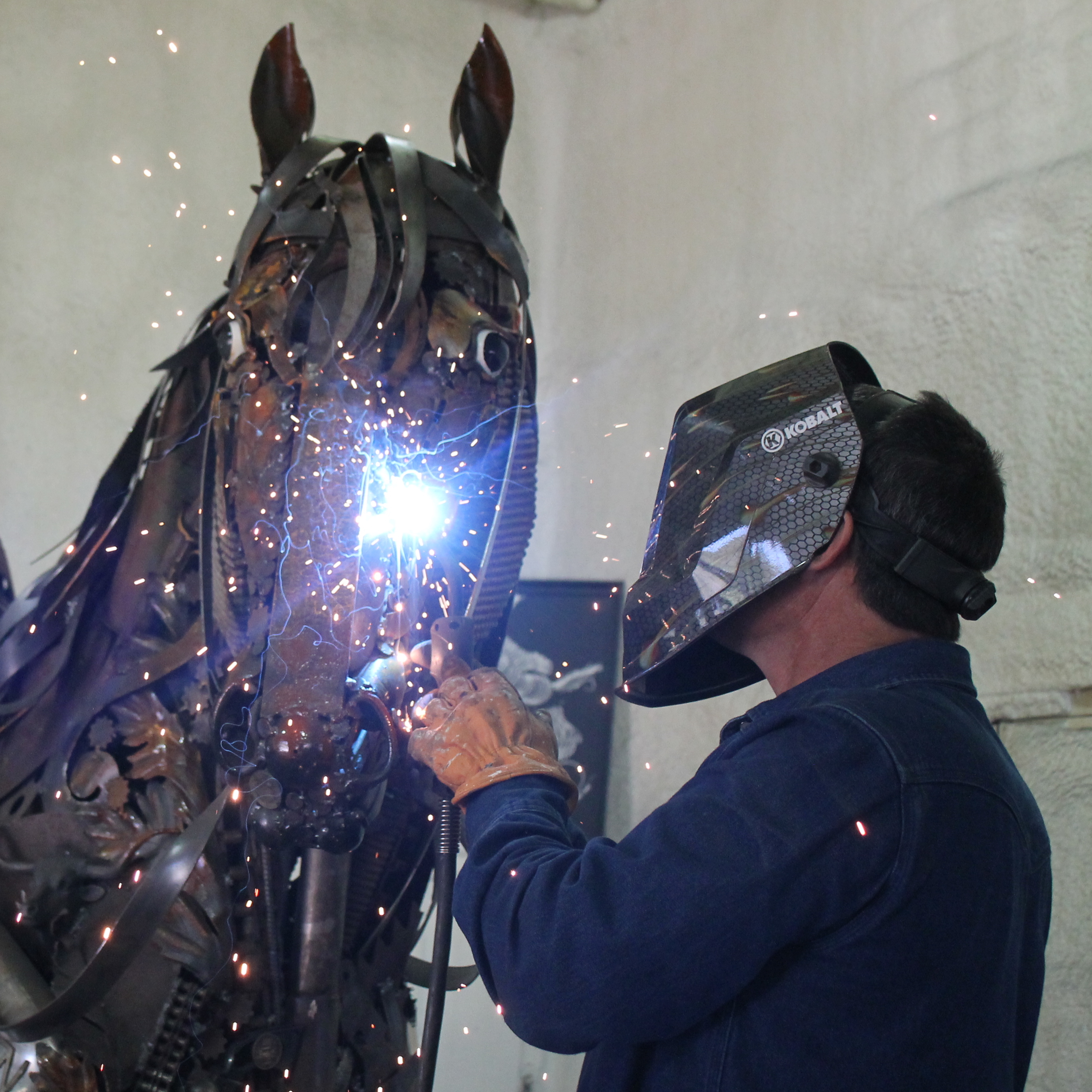 John Lopez welding a detail to his sculpture of Ed Lemmon atop his horse.