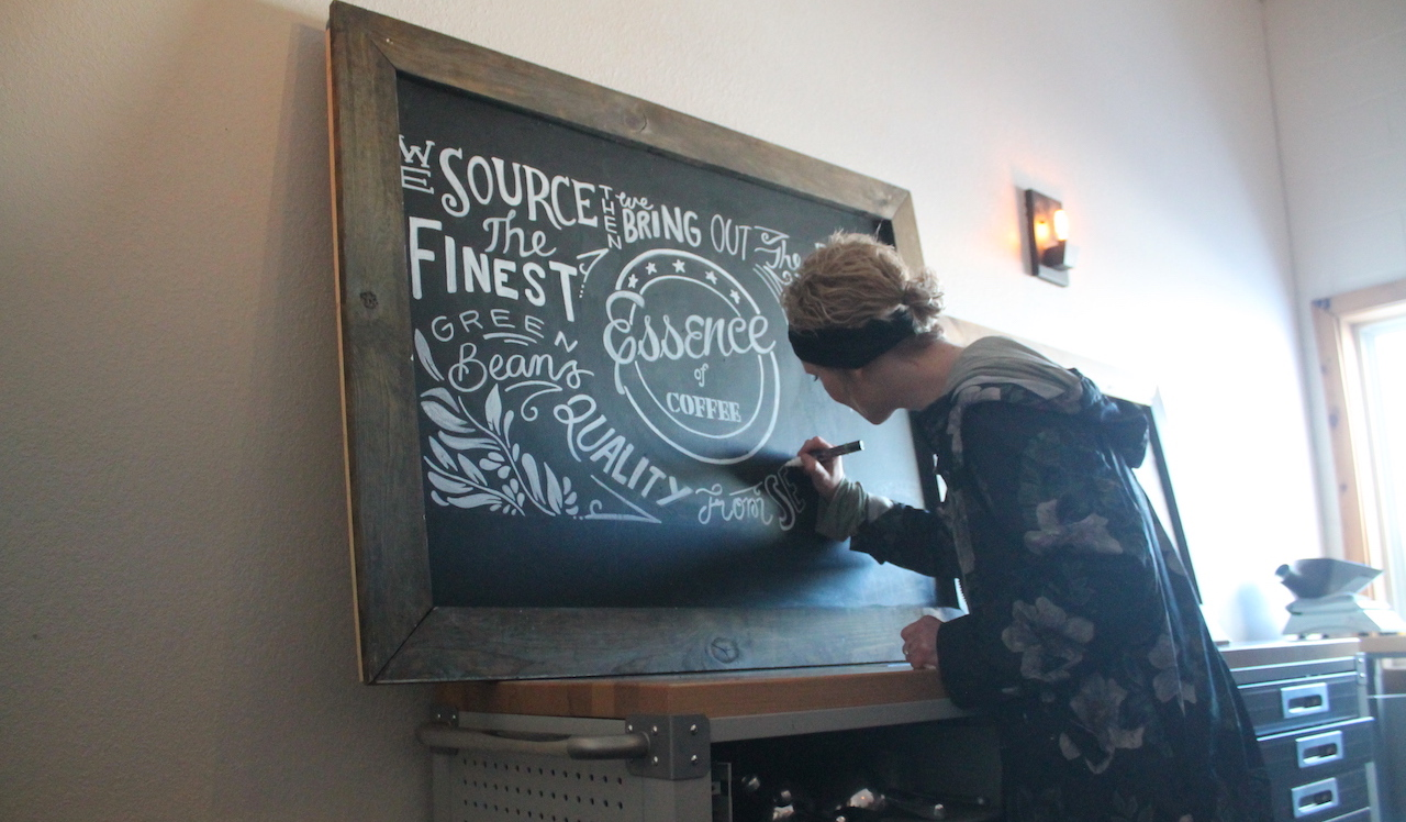 Christie Harris works on a chalk mural for Essence of Coffee.