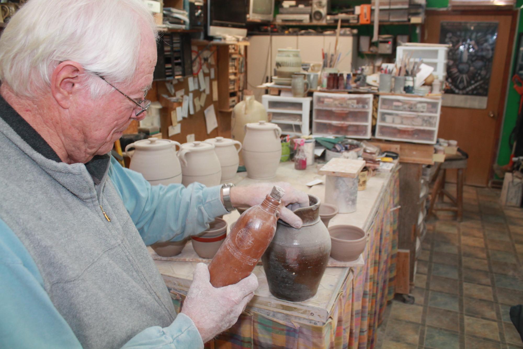 Huebner holds a nineteenth century salt fired German-made ceramic beer bottle.