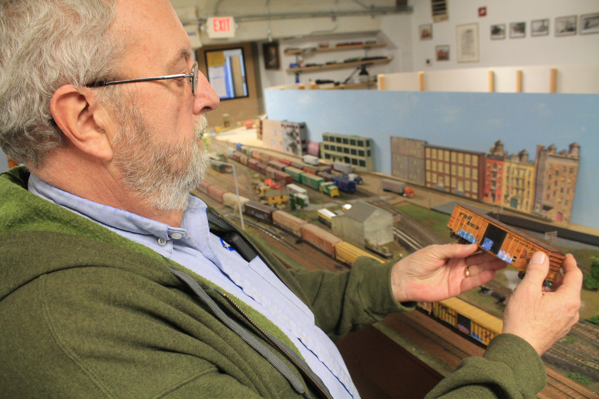 Charlie Davis inspecting one of his model boxcars, complete with realistic graffiti.