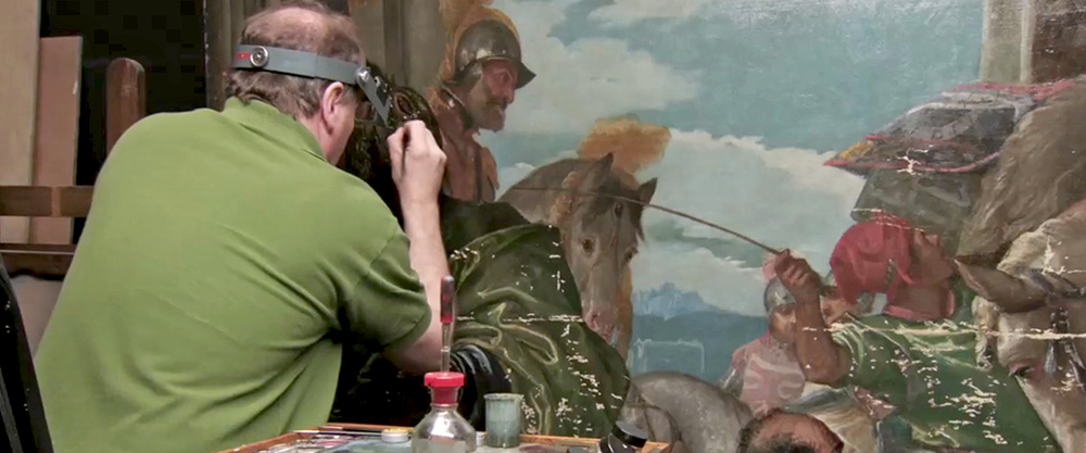 A restorer with a visor and his back to camera works on a detail of a large painting.