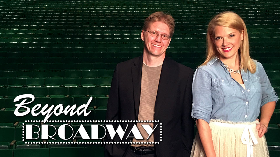 Hosts Joe Yezak and Emily Anderson stand in front of rows of theatre seats.
