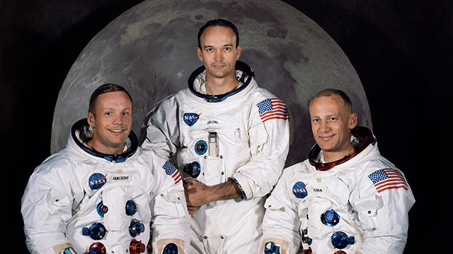 Apollo 11 crew Neil Armstrong, Michael Collins, and Buzz Aldrin wearing their space suits pose in front of a picture of the Moon