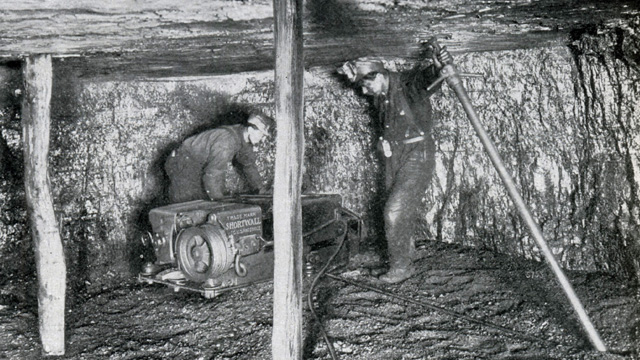 Miners in a coal mine set up an electric cutter.