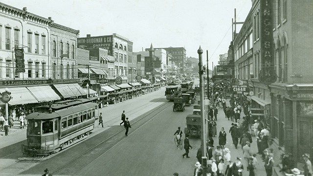 People, cable cars, and automobiles on Saginaw Street in Flint, Michigan, in the early 20th century.