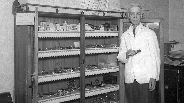 Dr. Wilke Drake stands next to a cabinet full of surgical equipment.