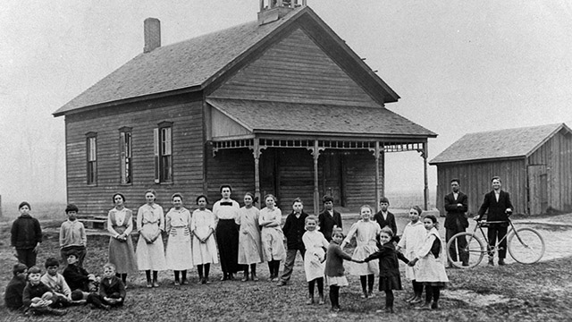 A class of children pose in front of a one-room schoolhouse.
