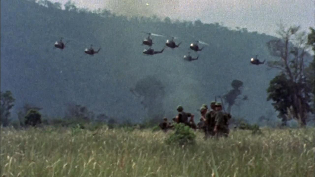 Soldiers cross a field as helicopters fly in the distance.
