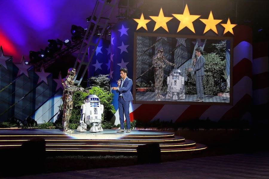 Emmy nominated actor and show host John Stamos on stage with Star Wars droids R2-D2 (C) and C-3PO (L) at <em>A Capitol Fourth</em> at U.S. Capitol, West Lawn on July 4, 2017 in Washington, DC. (Photo by Paul Morigi/Getty Images for Capital Concerts)