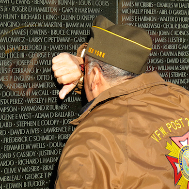 Man grieving at the Vietnam Memorial Wall