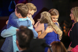 Actors Jason Dolley and Stefanie Scott hug honorees Cameron and Bayleigh Dostie on the 2015 National Memorial Day Concert.