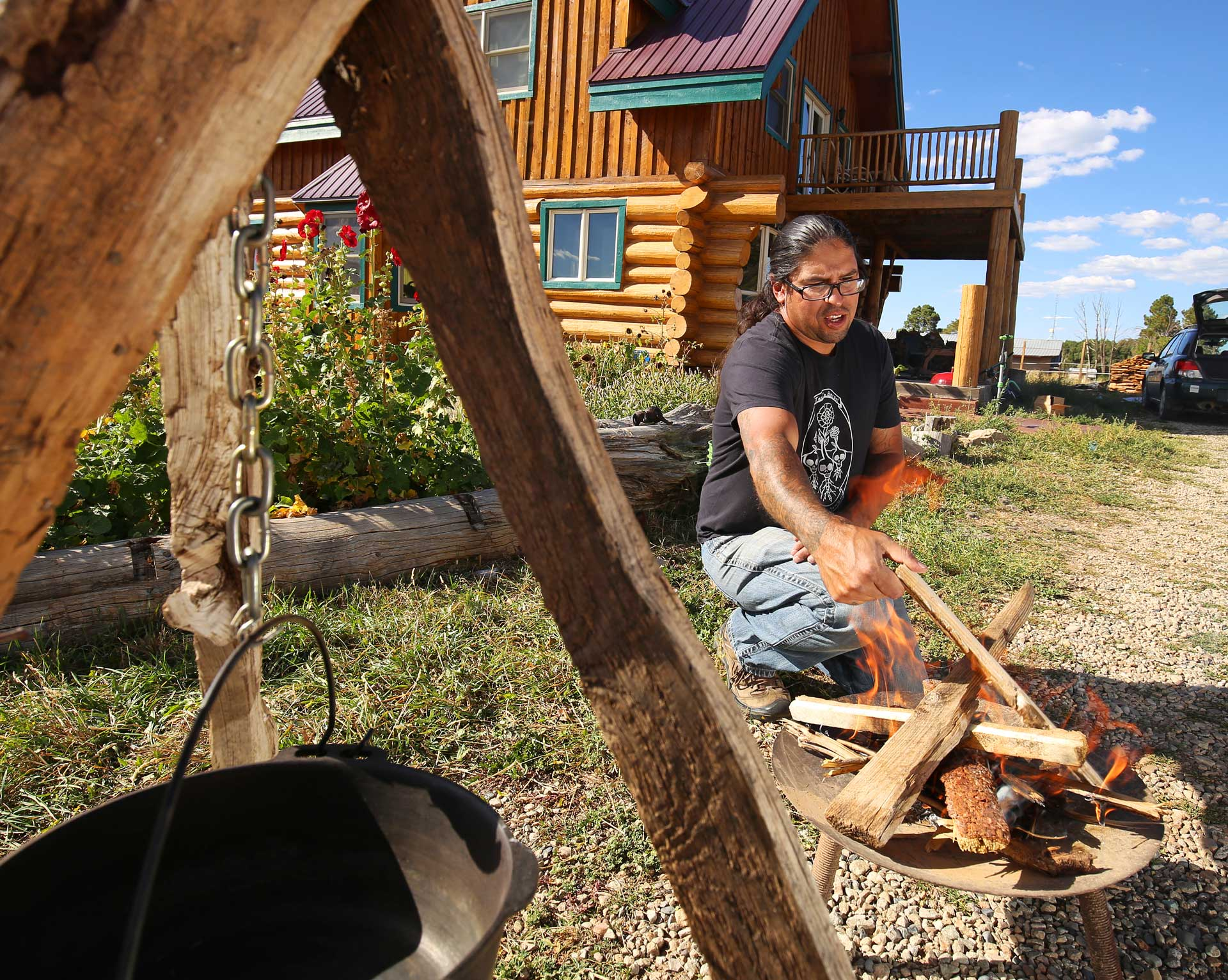 Karlos Baca makes a fire to roast and cook the Gete Okosomin squash for a coal-roasted squash bisque.