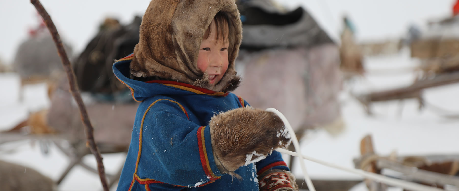 young child bundled up in warm clothing in snow